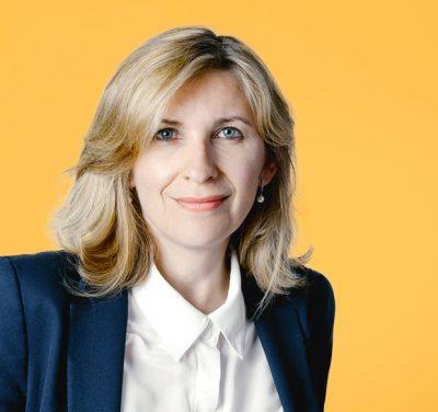 photographie-portrait-corporate-a-aix-en-provence-marseille-femme-veste-sombre-chemisier-blanc-bouton-sur-fond-jaune